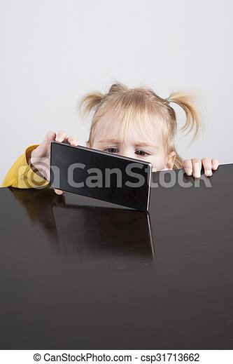 baby watching phone on table - csp31713662