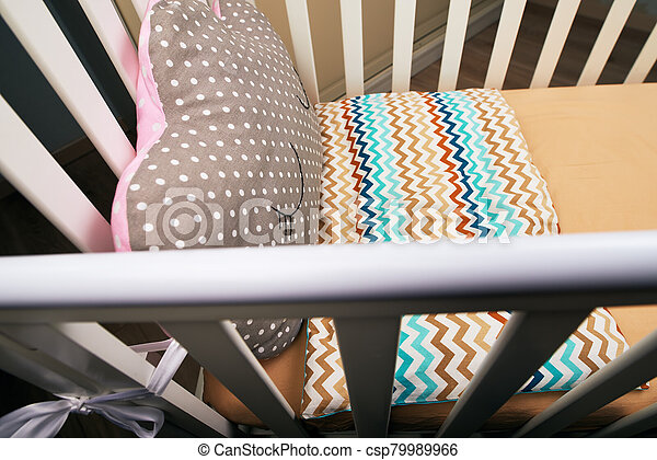 Baby white crib with a cute brown pink pillow with a can. brown mattress. Cozy bed for the baby - csp79989966
