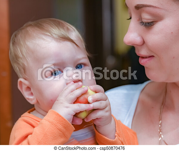 baby with a peach at mom's hands - csp50870476
