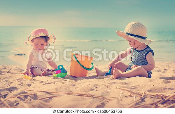 Babygirl and babyboy sitting on the beach - csp86453756
