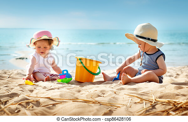 Babygirl and babyboy sitting on the beach - csp86428106