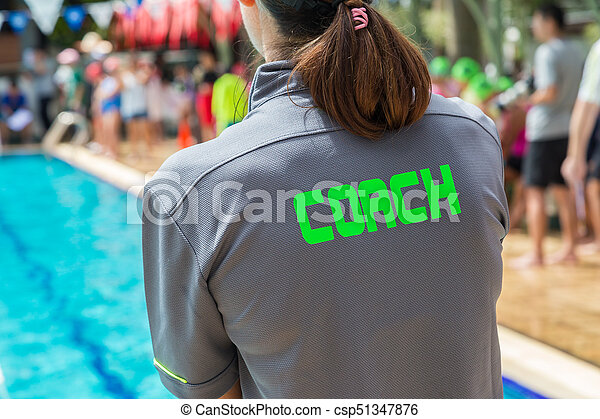 back of a swim coach's grey shirt with the green word Coach written on it - csp51347876