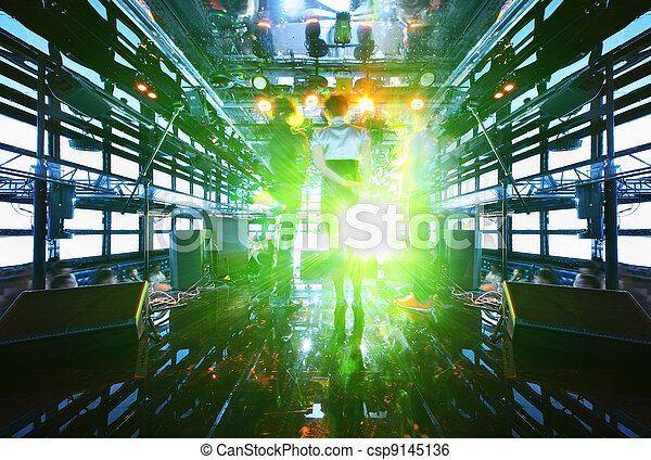 Back of people on stage at concert in nightclub, light show and loud music  - csp9145136