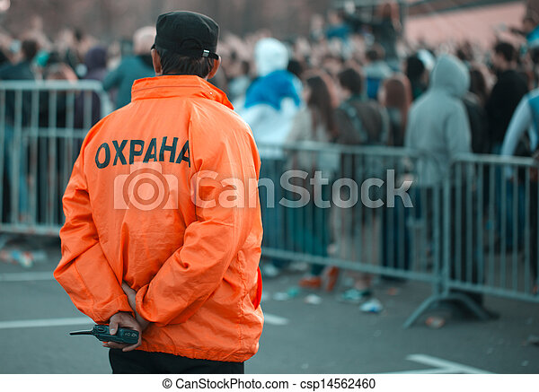 Back security guard in front of blurred crowd - csp14562460