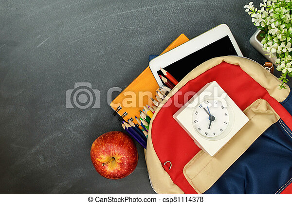 Back to school concept. Backpack with school supplies, clock, tablet and apple against chalk board. Top view. Copy space - csp81114378