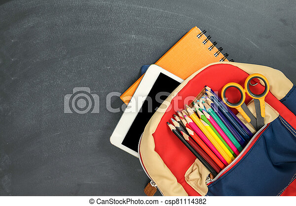 Back to school concept. Backpack with school supplies, tablet and against chalk board. Top view. Copy space - csp81114382