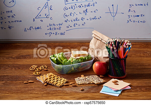 Back to School concept, school supplies, biscuits and lunchbox over white chalkboard, selective focus, close-up. - csp57575650