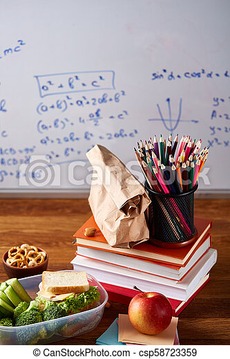 Back to School concept, school supplies, biscuits and lunchbox over white chalkboard, selective focus, close-up. - csp58723359