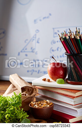 Back to School concept, school supplies, biscuits and lunchbox over white chalkboard, selective focus, close-up. - csp58723343