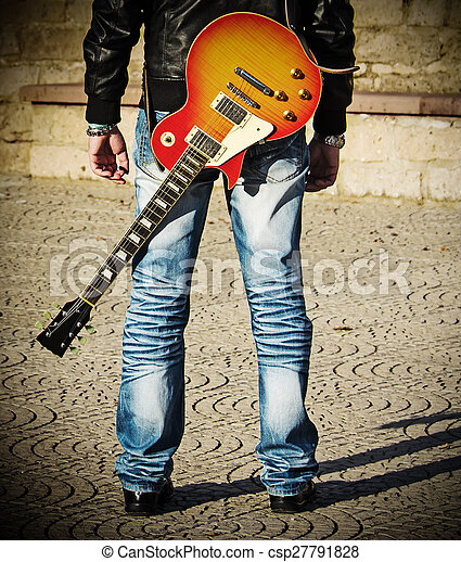 back view of a guitarist standing with a guitar - csp27791828