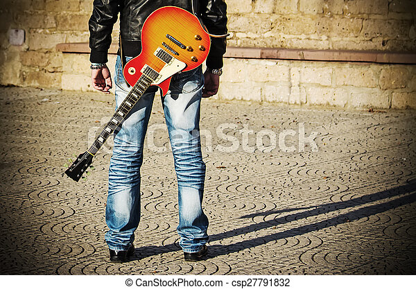 back view of a guitarist standing with a guitar - csp27791832