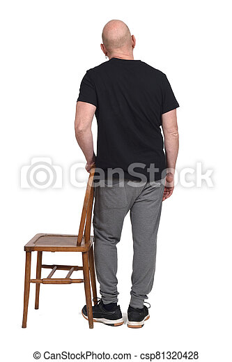 back view of a man standing with a chair in white background - csp81320428