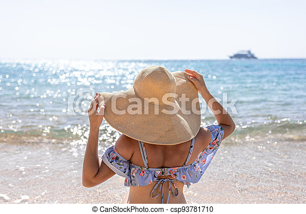 Back view of a woman in a big hat on the seashore. - csp93781710