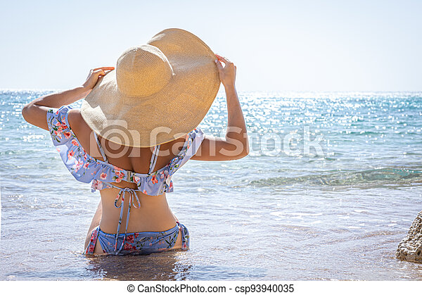 Back view of a woman in a big hat on the seashore. - csp93940035