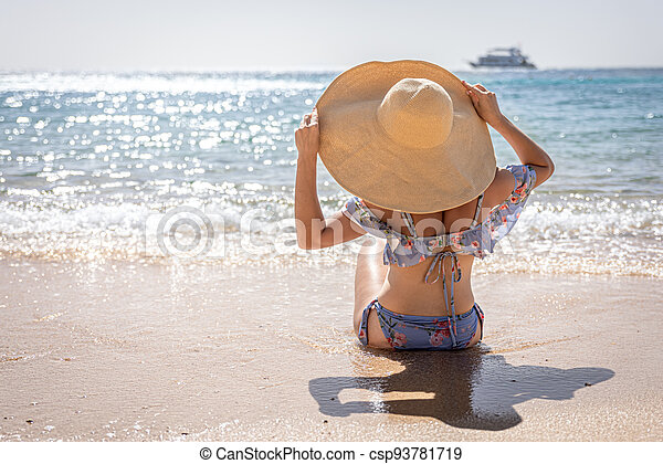 Back view of a woman in a big hat sits on the seashore. - csp93781719