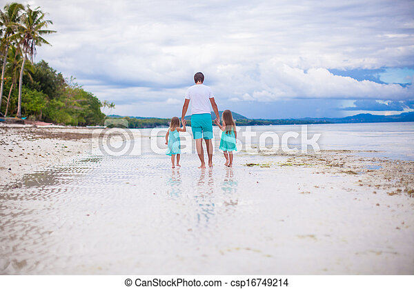 Back view of father and his two little daughters walking by the sea - csp16749214