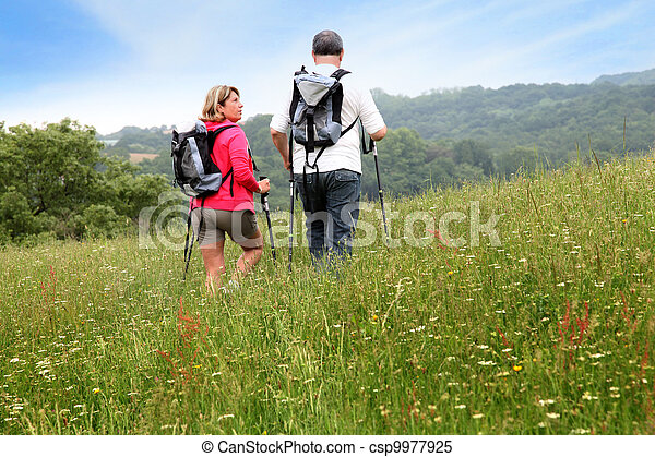 Back view of senior couple hiking in countryside - csp9977925