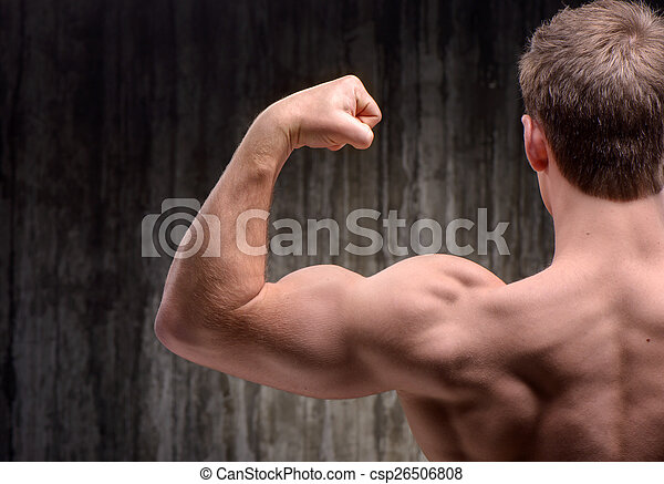 Back view of well formed man demonstrating biceps - csp26506808