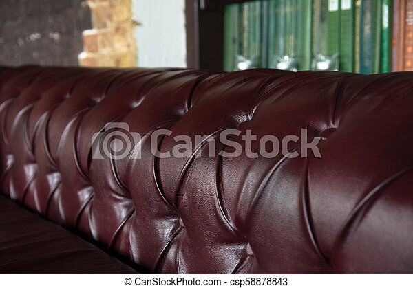 Background close-up burgundy leather sofa and bookshelf
