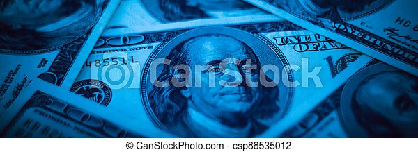 Background from dollars. Notes of one hundred American dollars are scattered across the background. - csp88535012