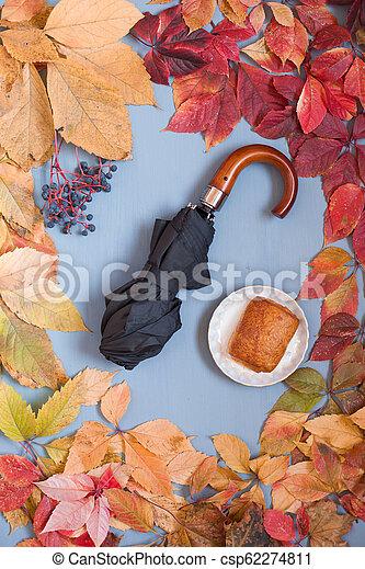 background of autumn yellow leaves and rain umbrella - csp62274811