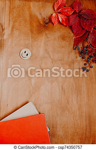 background of autumn yellow leaves and smiley and books - csp74350757