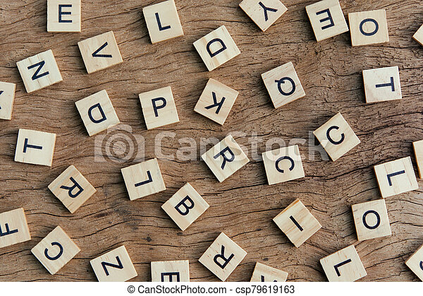 background of letterpress wood type printing blocks on wooden background, random letters of alphabet and punctuation stained by black inks - csp79619163