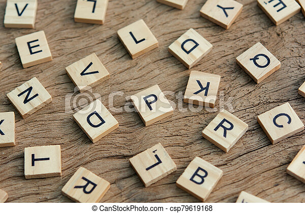 background of letterpress wood type printing blocks on wooden background, random letters of alphabet and punctuation stained by black inks - csp79619168