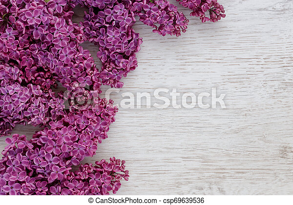 Background of lilac flowers on a wooden surface - csp69639536
