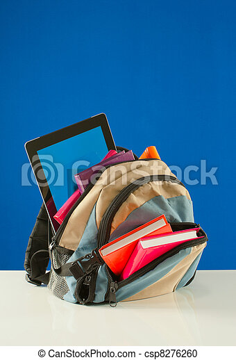 Backpack with colorful books and tablet PC on the blue background - csp8276260