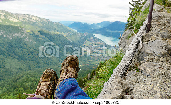backpacker shoes at the edge of a trail, a lake in the background - csp31065725