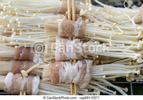 Bacon wrapped mushrooms is a street food in local market in Thailand, closeup. Thai food - csp69110371