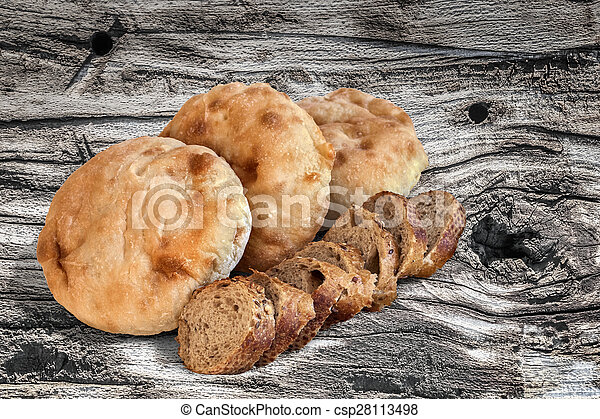 Baguette Integral Bread Slices with Pita Bread Loafs on old Wooden Table - csp28113498