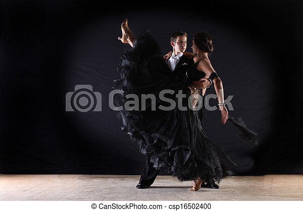 Bailarines latinos en el salón contra el fondo negro - csp16502400