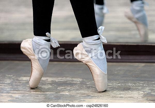 Cierra la vista a las bailarinas piernas en puntas en suelo de madera - csp24826160