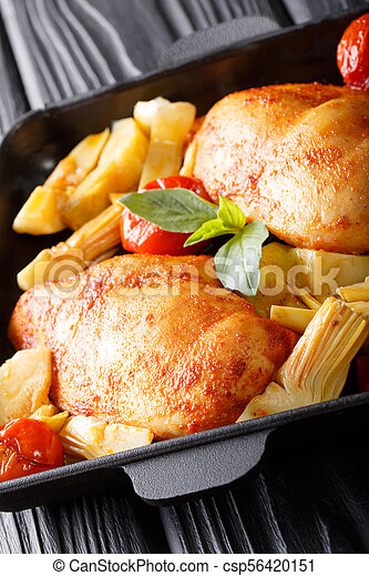 Baked chicken breast with garnish of artichokes and tomatoes close-up. vertical - csp56420151