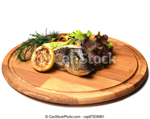 Baked fish with vegetables on a wooden board. - csp87839961