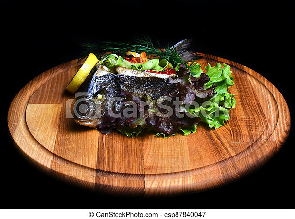 Baked fish with vegetables on a wooden board. - csp87840047