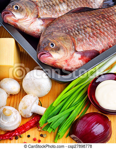 Baked fish with vegetables, sauce, red pepper on cutting board - csp27898778