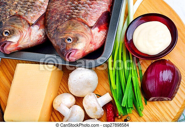 Baked fish with vegetables, sauce, red pepper on cutting board - csp27898584