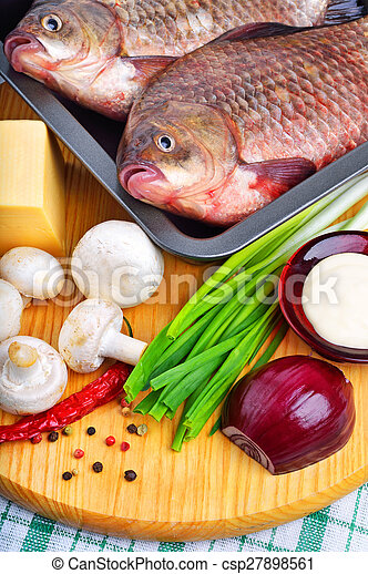 Baked fish with vegetables, sauce, red pepper on cutting board - csp27898561