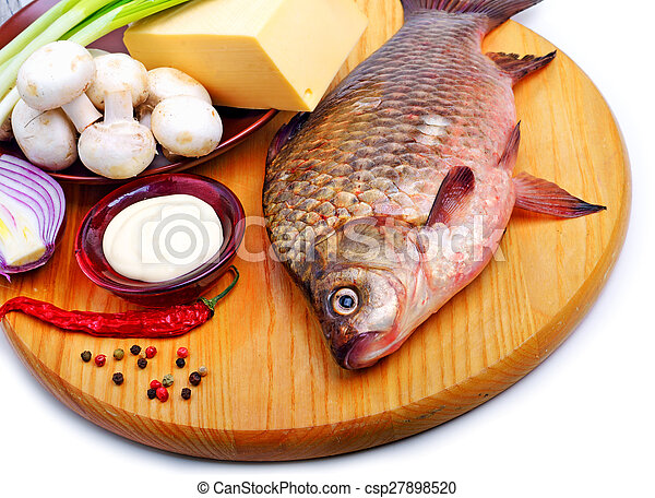 Baked fish with vegetables, sauce, red pepper on cutting board - csp27898520