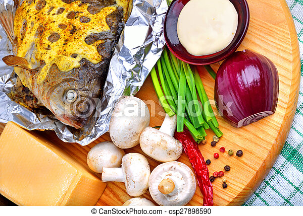 Baked fish with vegetables, sauce, red pepper on cutting board - csp27898590