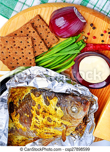 Baked fish with vegetables, sauce, red pepper, crisp bread on cutting board - csp27898599