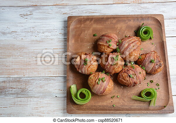 Baked, grilled baby potato wrapped in bacon - csp88520671