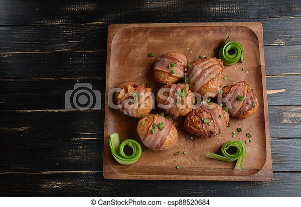Baked, grilled baby potato wrapped in bacon - csp88520684