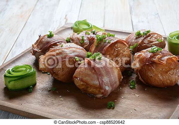 Baked, grilled baby potato wrapped in bacon - csp88520642