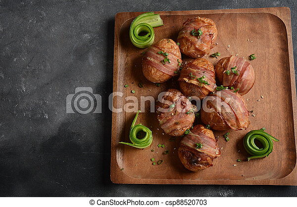 Baked, grilled baby potato wrapped in bacon - csp88520703