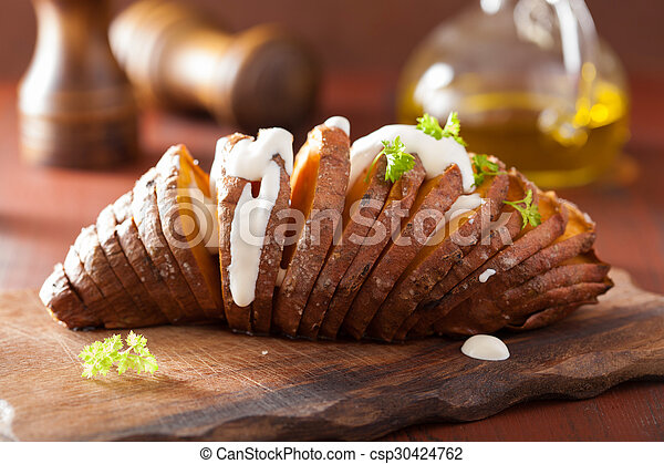 Baked hasselback potatoes with sour cream - csp30424762