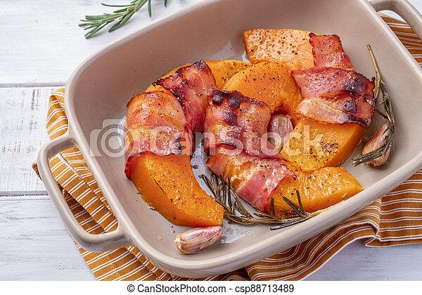 Baked pumpkin slices in bacon - csp88713489